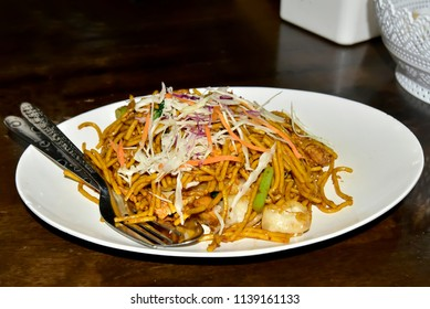 Spicy stir fried noodles with veggies and assortment of asian sauces served on wooden table. Known as Mee Goreng / Mi Goreng in Malaysia, Singapore and Indonesia.