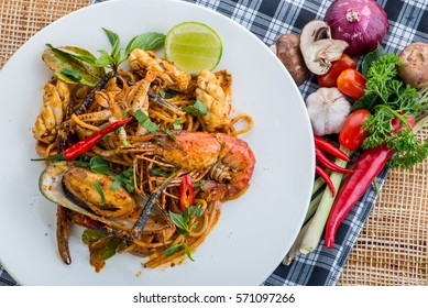 spicy stir fried spaghetti with seafood and basil leaves on white dish with spoon and fork, Thai fusion food with spaghetti on wooden table - Thai style