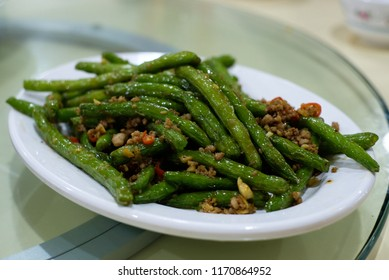 Spicy stir-fried green beans with minced pork on white plate.Famous Chinese cuisine.