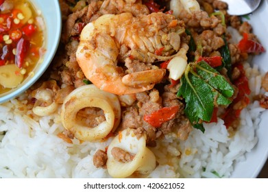 spicy stir-fried mixed seafood and chop pork with basil leaf on rice