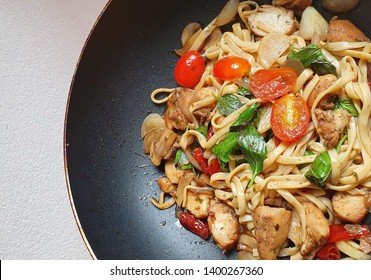 Spicy stir-fry konjac noodle with chicken breast ,tomato,vegetable,basil leaf,on black plate diet food concept