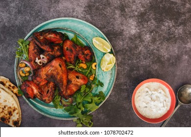 Spicy tandoori chicken wings with raita. Top view, blank space