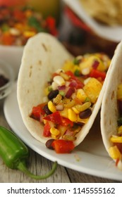 Spicy and Tangy Mango Salsa with tomatoes, mangoes, corn, beans, onions, jalapeno peppers, and wax moth larvae, wrapped in a flour tortilla