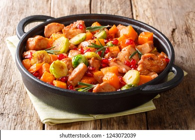 Spicy tasty chicken with vegetables with pomegranate sauce close-up in a frying pan on the table. horizontal