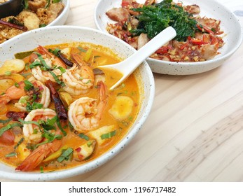 Spicy Thai food for lunch or dinner meal.  Tomyum soup and spicy stir fried with grill pork on the table.
