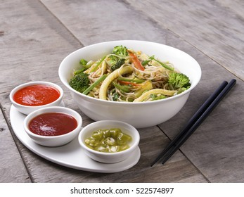 SPICY THAI NOODLES WITH GREENS SERVED IN A WHITE BOWL WITH TOMATO SAUCE CHILLI SAUCE AND VINEGAR CHILI SAUCE ON WOODEN BACKGROUND