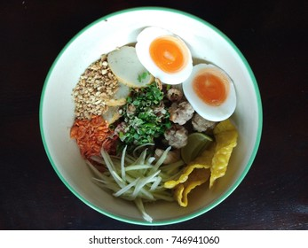 Spicy Thai Noodles with Pork and Boiling Egg in a White bowl