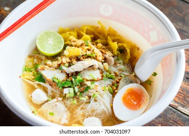 Spicy Thai Noodles or tom yum with boiled egg on the wooden table, Thai food
