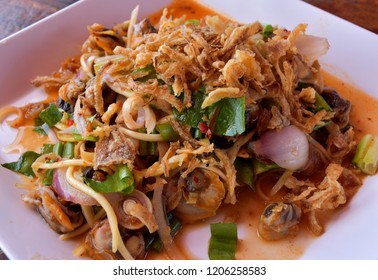 A spicy Thai salad made with blood cockles or Cockle salad on wood table, Thai food.