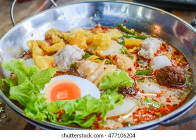 Spicy Thai Tomyum noodle with pork, vegetable, egg and balls in a metal bowl.