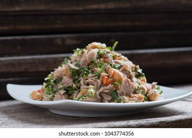 Spicy tuna salad on wooden table background