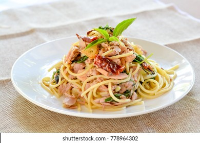 Spicy tuna spaghetti with red dried chillies and sweet basil leaves on white dish.