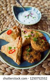 Spicy vegetable Indian snacks -  pakora, samosa, onion bhaji. Pakora, also called pakoda, pakodi, fakkura, bhajiya, bhajji or ponako sambusa, sambuus, samoosa, or samboksa is a food fried pastry.