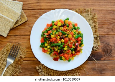 Spicy vegetable stew on a white plate and a wooden table. Mixed vegetable stew. Stewed carrots, green beans, red beans, peas, corn, pepper and onions. Healthy food. Top view