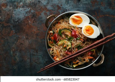 Spicy veggie wok: rice noodles with zucchini, onion and sesame. Asian styled lunch on metal textured background. Vertical composition with copy space for text