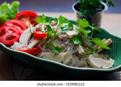 Spicy vietnamese sausages salad placed in a leaf-shaped green plate. With onion, garlic, red pepper on a black wooden table