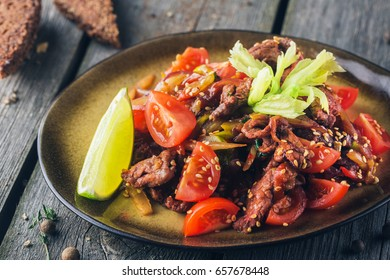 Spicy-sweet beef with zucchini, paprika, celery stalk, tomatoes under spicy sesame dressing