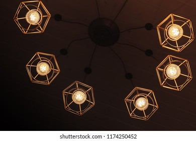 Spider type ceiling chandelier with hanging  bulb lamps, yellow LED lighting elements
