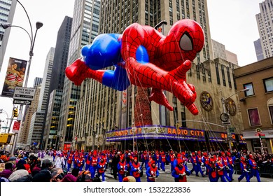 Spiderman balloon floats in the air during the annual Macy's Thanksgiving Day parade along Avenue of Americas with the Radio Music Hall in the background. Manhattan, New York, USA - November 27, 2014.