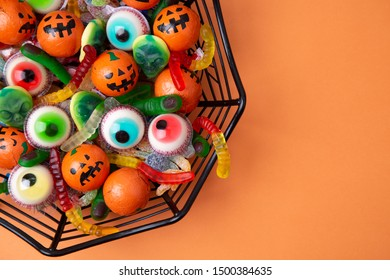 Spiderweb shaped bowl full of candy and chocolate with shape of eyes, worms, fingers, spiders and monsters on an orange background. Top view