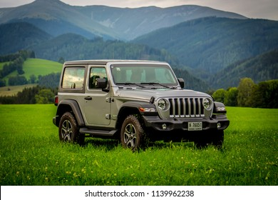 Spielberg / Austria - 07/17/2018: The new Jeep Wrangler JL Sport off-road with mountains in the background