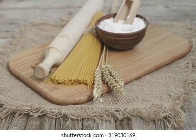 Spikelets of wheat and flour in a bowl on a flour table. Close up. rustic style