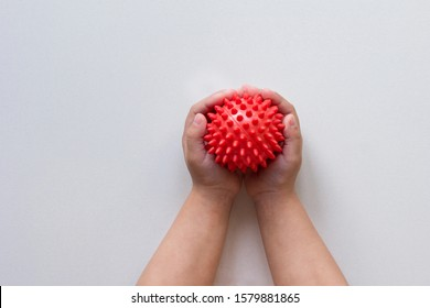 Spiky red massage needle ball in child hands on white background