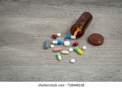 Spill background on a wood table that spilling out of pill bottle.