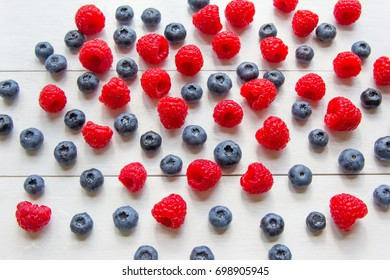 Spilled assortment of raw fresh berries: raspberry and blueberry at white wooden background