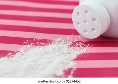 Spilled baby scented powder on striped background with short depth of field