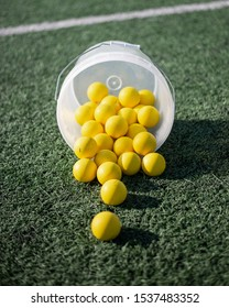 A spilled bucket of women's, yellow lacrosse balls on a turf lacrosse field.