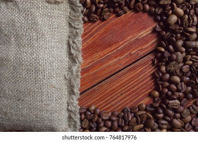 Spilled coffee beans frame over old wooden table
