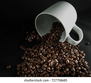 Spilled coffee beans on a black background with a white mug
