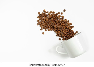 Spilled coffee beans from the white ceramic cup isolated on white background