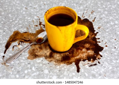 Spilled coffee on kitchen table with yellow mug and teaspoon. Focus on spoon.