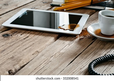 Spilled coffee on white tablet computer on the office table. Copy space. Free space for text