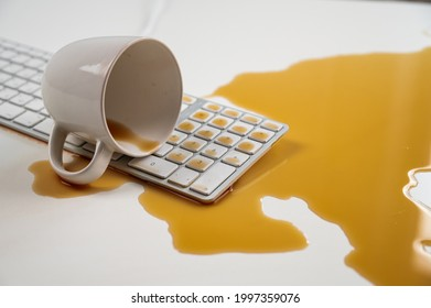 Spilled cup of black coffee on computer keyboard on white table.