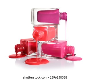 Spilled different nail polishes with bottles on white background