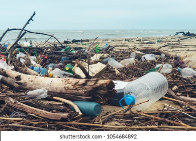 Spilled garbage on the beach of the big city. Empty used dirty plastic bottles. Dirty sea sandy shore the Black Sea. Environmental pollution. Ecological problem. Bokeh moving waves in the background