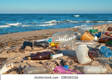 Spilled garbage on the beach of the big city. Empty used dirty plastic bottles. Dirty sea sandy shore the Black Sea. Environmental pollution. Ecological problem