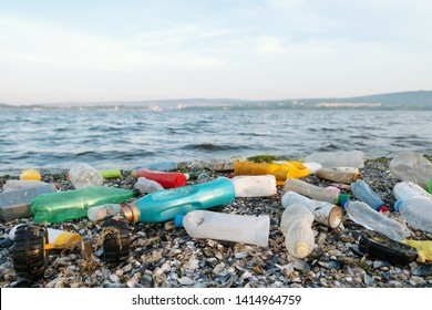 Spilled garbage on the beach of a big city. Empty used dirty plastic bottles, children's plastic toys. Dirty sea, sandy coast the Black Sea. Environmental pollution. Ecological problem. Moving waves