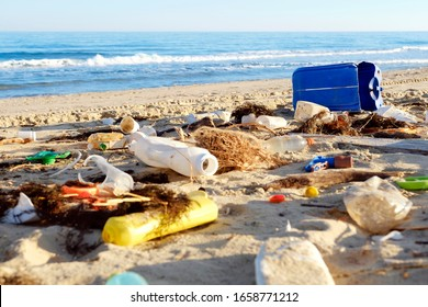 Spilled garbage on beach of big city. Blue plastic tank. Empty used dirty plastic bottles. Dirty sea sandy shore the Black Sea. Environmental pollution. Ecological problem. Bokeh moving waves