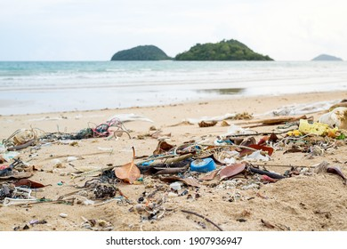 Spilled garbage on the beach. Empty used dirty plastic bottles. Environmental pollution. Ecological problem