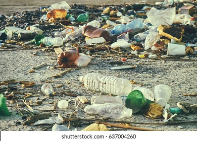 Spilled garbage on the street of a big city. Empty used dirty plastic bottles. Dirty sea sandy shore of the Black Sea. Environmental pollution. Ecological problem