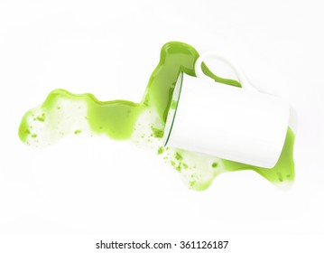 spilled green tea from a cup isolated on white