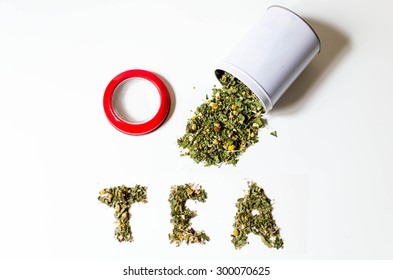 Spilled loose tea pot with a red lid on a white background