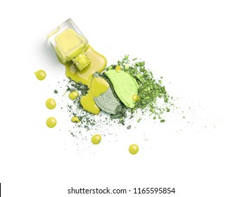 Spilled nail polishes bottles on lime and yellow eye shadows cosmetic. Isolated on white. Creative cosmetic concept.