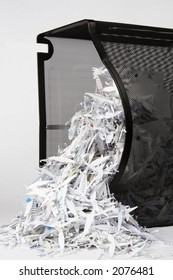 A spilled over paper shredder waste basket