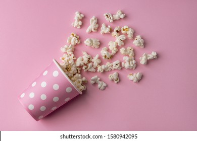 Spilled popcorn on a pink background, cinema, movies and entertainment concept