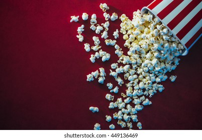 Spilled popcorn on a red background, cinema, movies and entertainment concept - Shutterstock ID 449136469